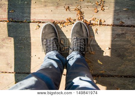Legs in trousers and black sneakers on wooden floor with orange leaves