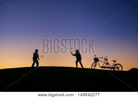 Couple is playing badminton. People on evening sky background. Play until you win. Test of endurance.