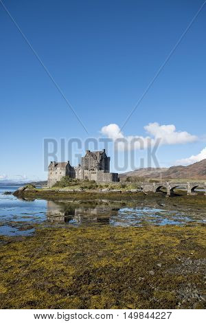 Popular tourist destination of Eilean Donan Castle Scotland beautiful 13th century fortification at Dornie Kyle of Lochalsh in the Scottish Highlands with clear blue sky and reflections