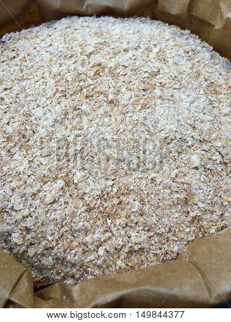Wheat bran in a brown paper bag in closeup