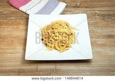 Dish of Spaghetti Carbonara Shrimp on wood background.