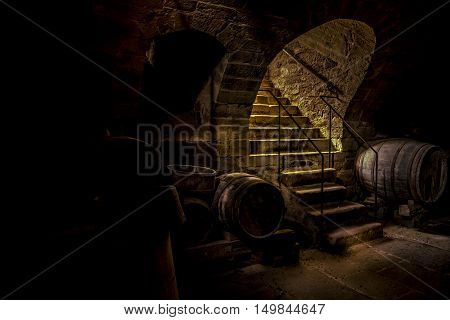 Wine cellar in low light - Couple of big wooden barrels stored in an antique wine cellar in a small village in Germany