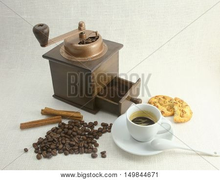 Coffee Cup, Biscuit, Grinder And Coffeebeans On Table