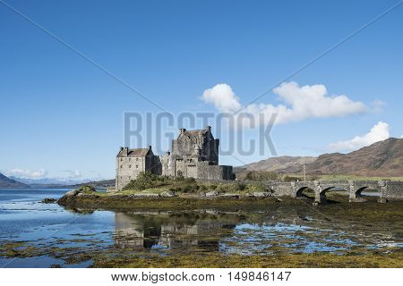 Iconic Scottish scene of Eilean Donan Castle beautiful 13th century fortification at Dornie Kyle of Lochalsh in the Scottish Highlands with clear blue sky and reflections