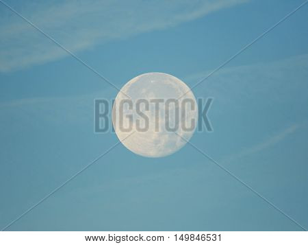Full moon in daytime on a blue sky and soft clouds