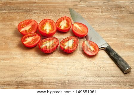 Close up knife and tomato on wooden table
