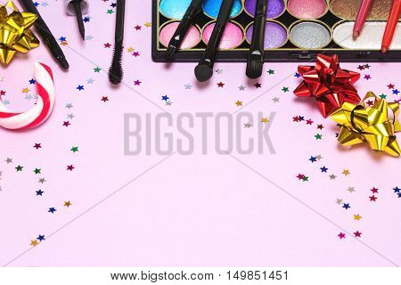 Christmas party makeup. Bright color glitter eyeshadow, mascara, eyeliner, lip gloss, lip liners, applicator, brushes with candy cane, gift wrap bows and confetti. Shallow depth of field. Copy space
