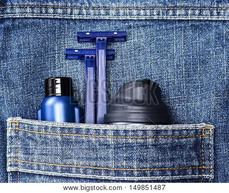 Mens cosmetics. Shaving foam, disposable razors and aftershave lotion in jeans pocket. Basic skin care cosmetic products and accessories for men. Toiletry and cosmetic travel kit