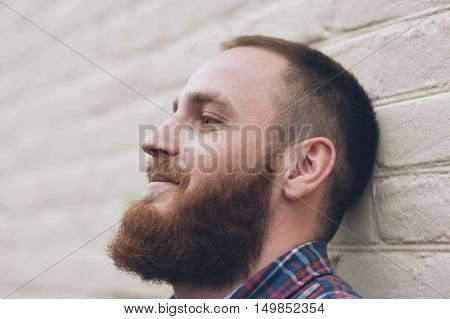 portrait of a dreaming man with a beard in front of the white brick wall