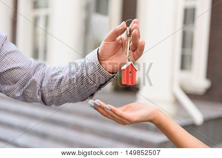 Deal is completed. Close up of keys in hands of professional realtor holding them and giving to new owner of apartment