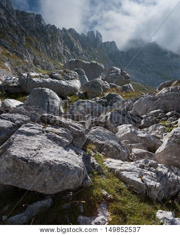 Harsh mountainous terrain full of rocks and stones with high peaks in the background.
