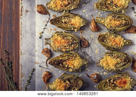 Artichokes baked with cheese garlic and thyme on a baking sheet top view.
