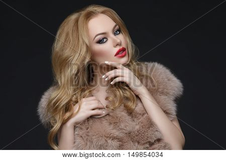 Beautiful young woman with bright makeup, red lips and long blond hair standing in fur coat. Studio shot over dark background. Copy space.