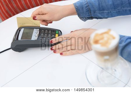 So easy to pay. Top view of woman putting her credit card through electronic reader to pay bill in coffee shop