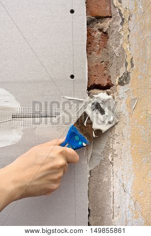hand plastering wall with spatula during repair