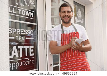 What can I get for you today. Shot of young smiling barista ready to take order from customer at cafe outside