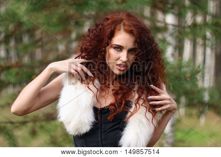Young woman in corset with fur and curly hair depicts animal grin in autumn forest