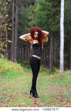 Pretty young woman in corset with fur stands in autumn forest at sunny day