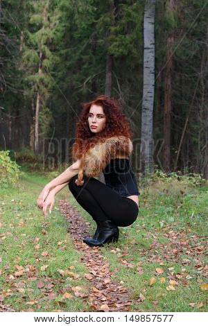 Pretty young woman in corset with fur squatting in autumn forest at sunny day