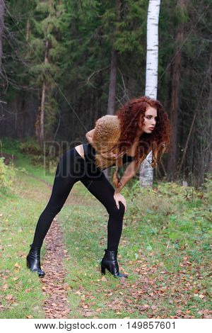 Pretty young woman in corset with fur pose in autumn forest