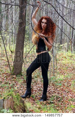 Pretty young woman poses with tree branches in autumn forest