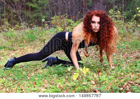 Beautiful girl with curly hair poses on grass in autumn forest