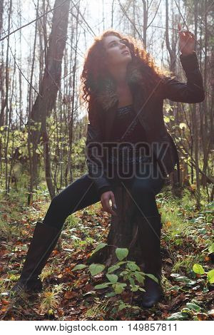 Beautiful girl in boots and jacket sits on tree stump and touches branch in sunny autumn forest