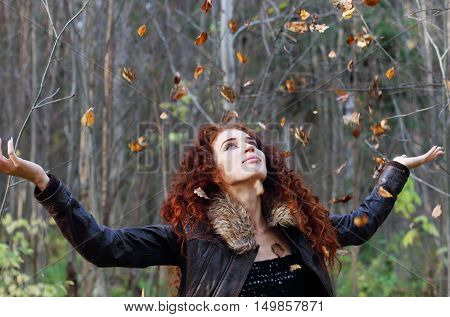 Beautiful woman with curly hair in leather jacket throws up dry leaves in sunny autumn forest