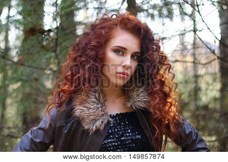 Beautiful woman with curly hair in leather jacket in sunny autumn forest shallow dof