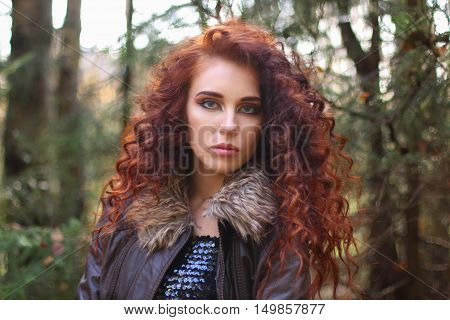Woman with curly hair in leather jacket in sunny autumn forest shallow dof