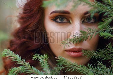 Beautiful woman looks through fir branch in forest close up shallow dof