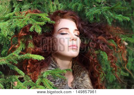 Young pretty woman with closed eyes among fir branches in forest close up