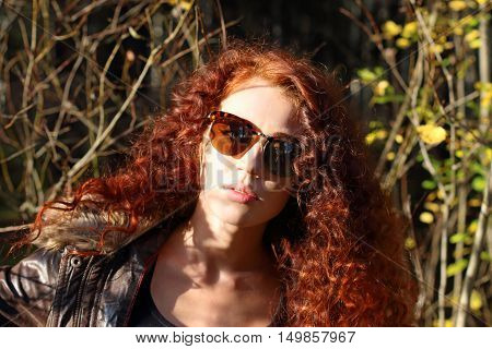 Pretty woman in sunglasses at sunny day in autumn forest