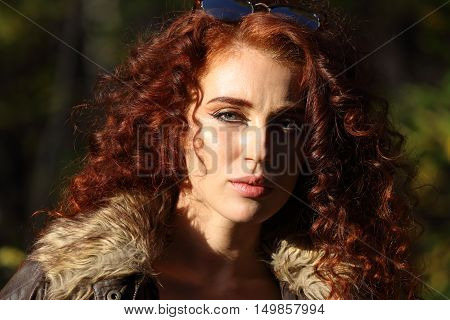 Pretty woman with sunglasses at sunny day in autumn forest shallow dof