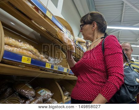 Alushta, Russia - June 10, 2016: Mature woman chooses bread in a supermarket department PUD