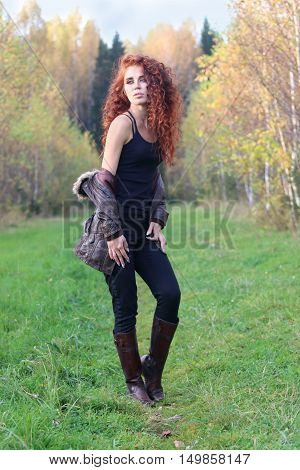 Beautiful woman in leather boots stands on grass in autumn forest