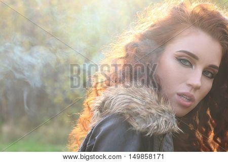 Beautiful woman with red hair in jacket among smoke in sunshine shallow dof