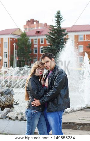Man embraces woman in black leather jackets near fountain in autumn park