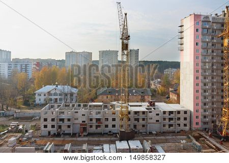 Construction site with cranes and part of concrete panel building at fall day
