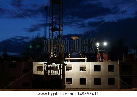 Crane downs slab workers on building under construction at night