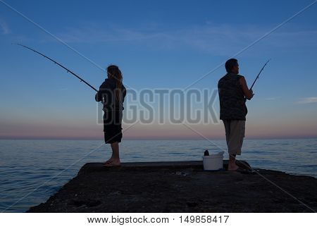 Men at sunset to catch the bait fish from the pier