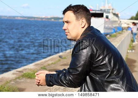 Man in leather jacket stands near river with ship looks away and dreams