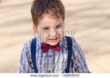 Handsome little boy with bow tie looks at camera outdoor top view
