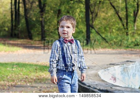 Smiling little boy with bow tie and jeans poses in sunny green park