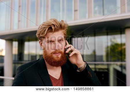 Guy in casual wear talk by phone. Man in dark suit and red t-shirt open for conversation. Business building background in big city.