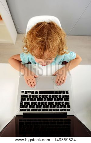 learning and next generation concept, top view of a kid looking into laptop