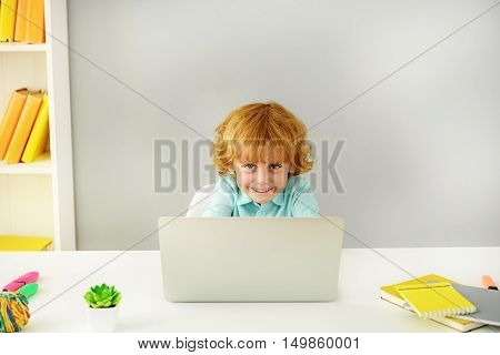 learning and next generation concept, young boy smiling in front of notebook