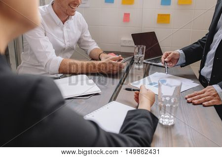Close up of businessman explaining a financial plan to colleagues at meeting. Business people discussing a financial plan around a table.