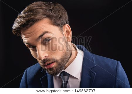 Pensive man is staring at something with concentration. He is standing in formal suit. Isolated