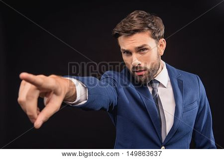 Hey you. Serious young businessman is pointing finger forward with authority. Isolated on black background